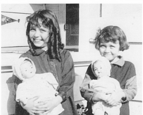 Two sisters show off their Depression-era Christmas presents: Bye-Lo Baby Dolls.